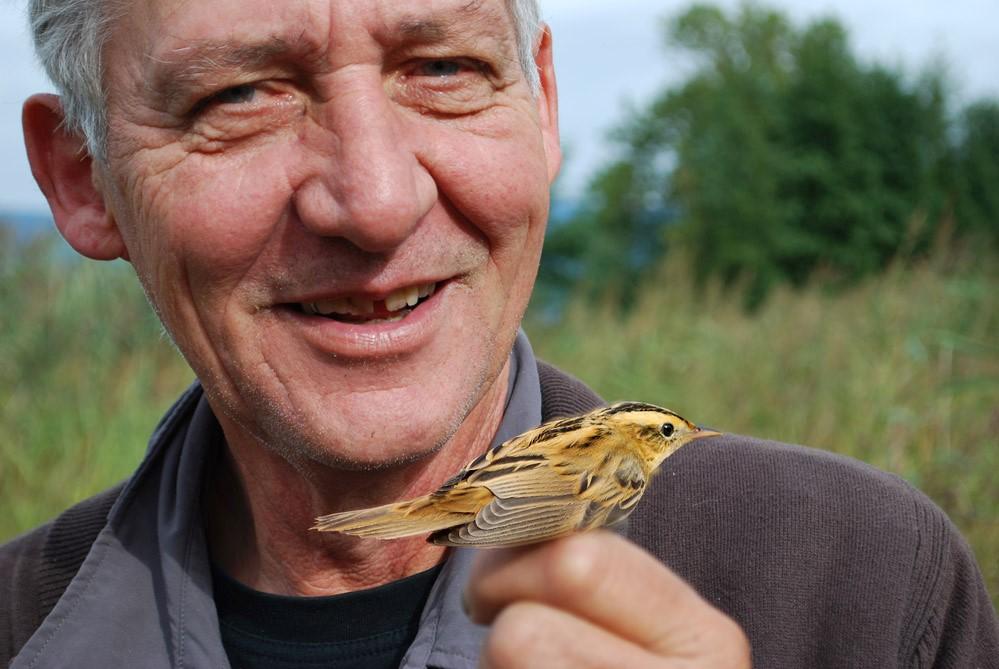 Michel Antoniazza sourit en montrant un petit oiseau brun et jaune qu'il tient dans ses mains.
